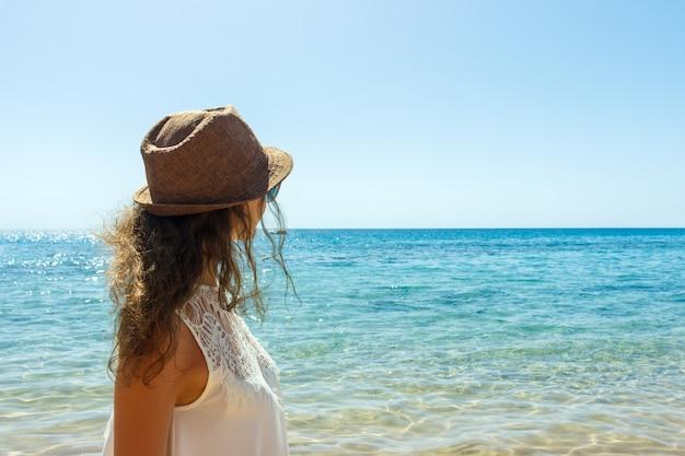 Garota solitária, olhando para o mar calmo com o vento em seu mar de cabelo