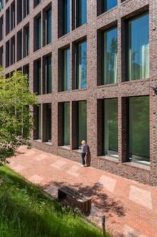 Garota solitária, olhando para o telefone em um grande prédio de tijolos com grandes janelas.