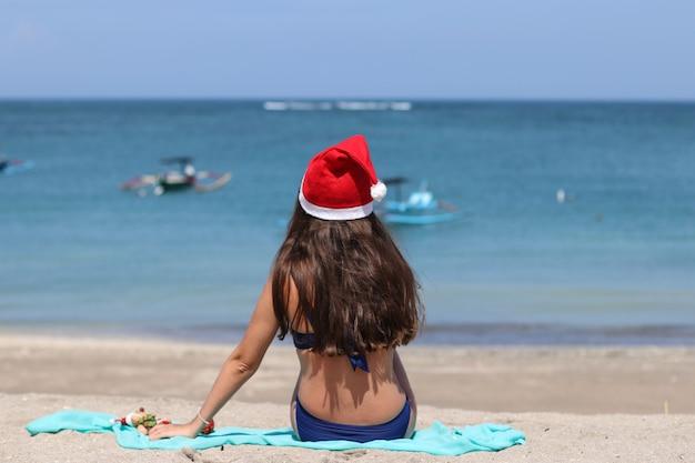 Garota solitária sentada na praia com um chapéu vermelho de natal