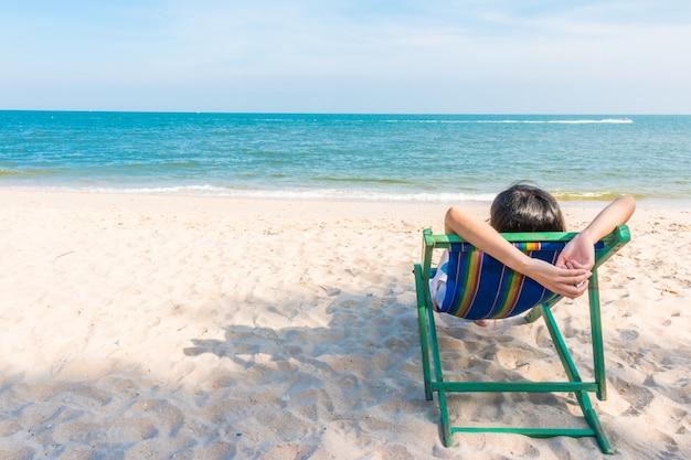 Garota solitária sentado na cadeira de praia de madeira no fundo da praia