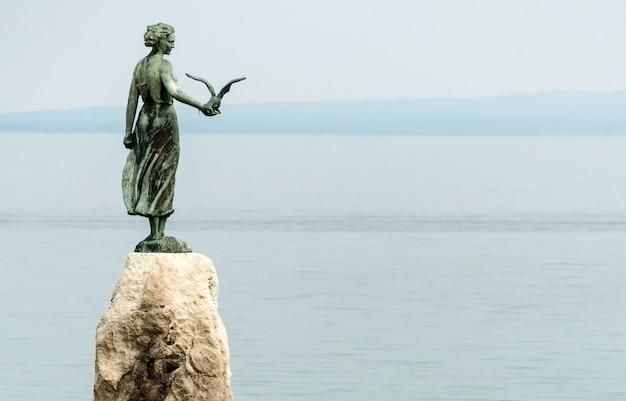 Garota solteira segurando uma gaivota e de frente para o mar, estátua em rochas, opatija