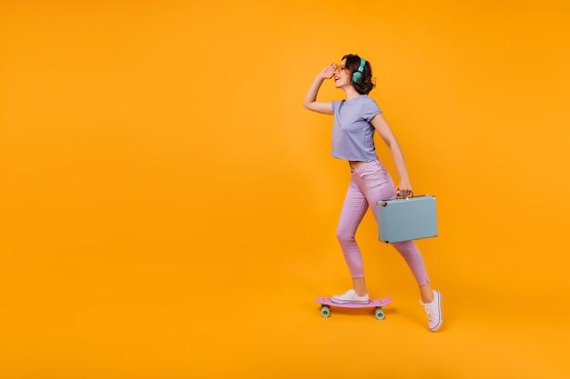 Garota sonhadora em calças rosa de pé no skate e ouvindo música. modelo feminino encaracolado inspirado em fones de ouvido posando com valise azul.