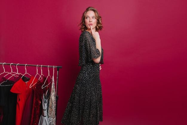 Garota sonhadora olhando para longe e pensando no que vestir, em pé no camarim