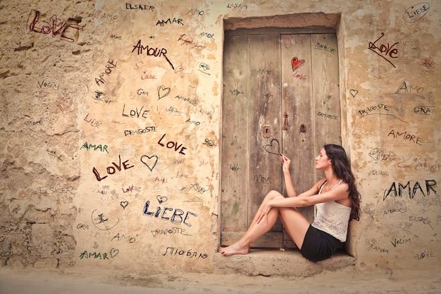 Garota sonhando com amor em uma porta velha no verão
