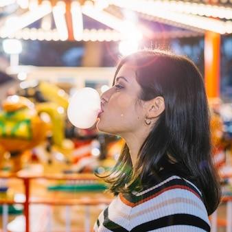 Garota soprando goma de mascar