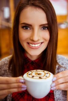 Garota sorri e bebe um café delicioso.