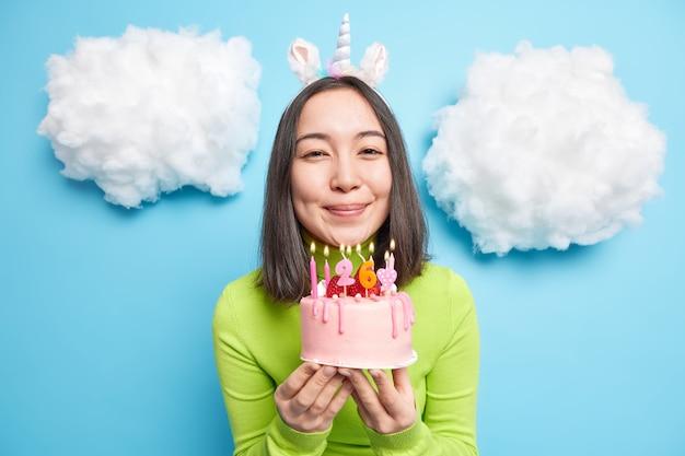 Garota sorri gentilmente segura um bolo delicioso com velas e convida você para uma festa olha feliz para as poses da câmera internas em azul