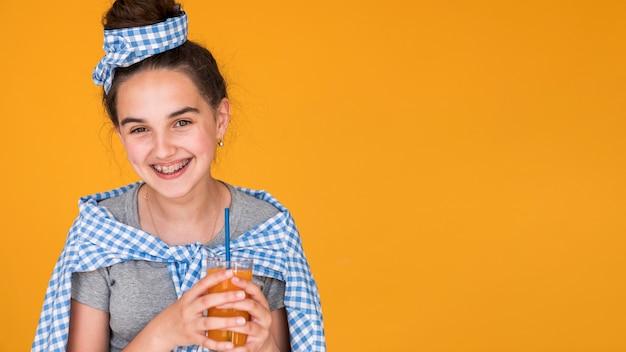 Garota sorridente, apreciando seu suco de laranja