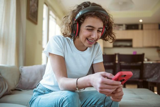 Garota sorridente com fones de ouvido enviando mensagens no telefone