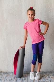 Garota sorridente confiante com a mão no quadril segurando rolando esteira de exercício