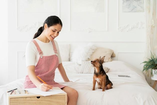 Garota sorridente de tiro médio com cachorro escrevendo