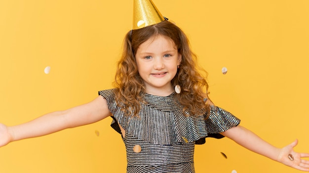 Garota sorridente de tiro médio com chapéu de festa