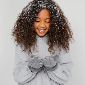 Garota sorridente de tiro médio com neve