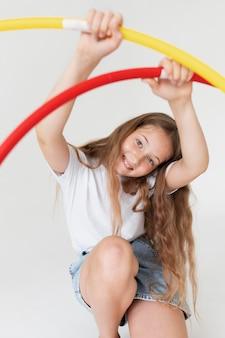 Garota sorridente de tiro médio segurando círculos