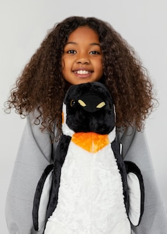 Garota sorridente de tiro médio segurando um pinguim