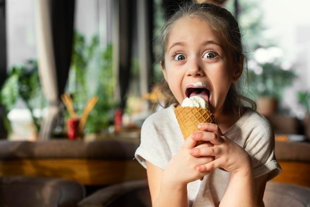 Garota sorridente de tiro médio tomando sorvete