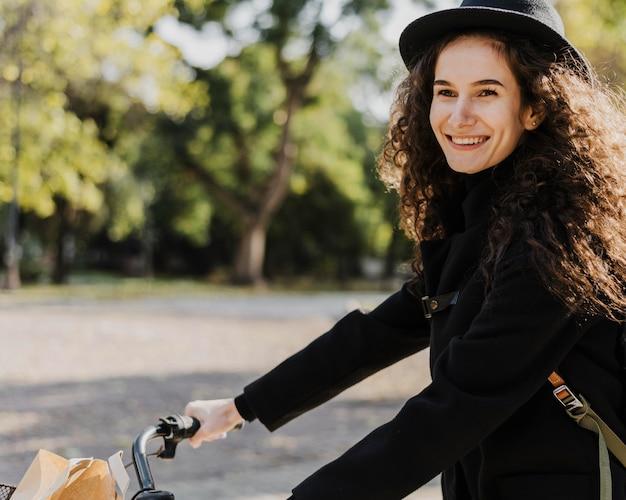 Garota sorridente de transporte alternativo de bicicleta