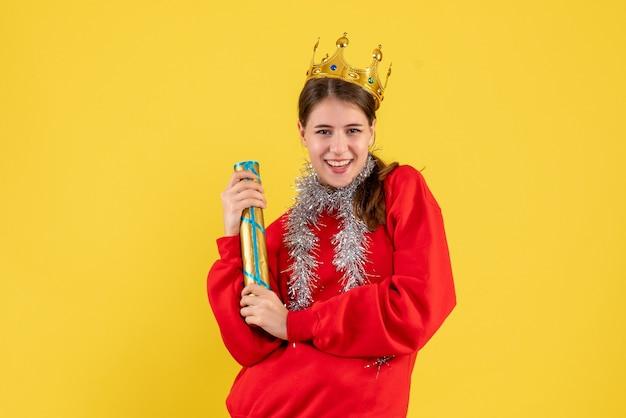 Garota sorridente de vista frontal com suéter vermelho segurando um popper de festa