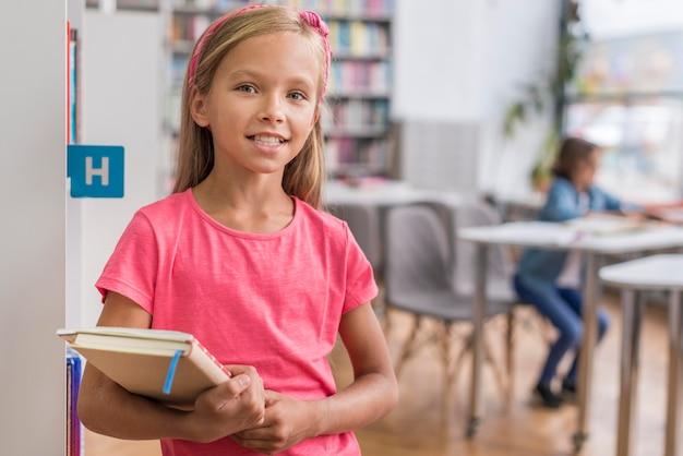 Garota sorridente de vista frontal segurando um livro e um caderno