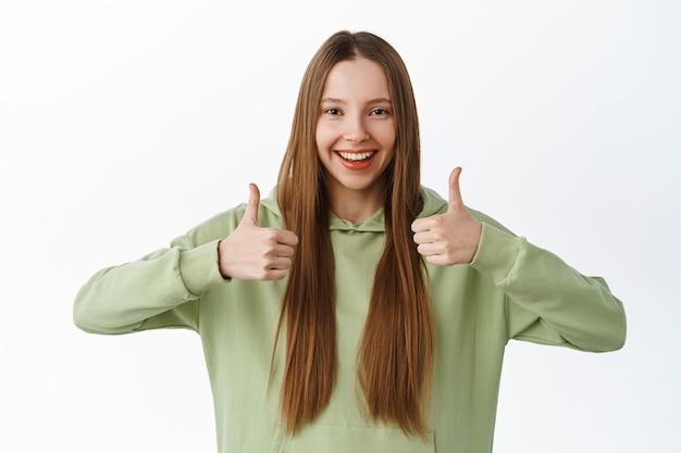 Garota sorridente e confiante mostra polegares para cima em aprovação e apoio, diga sim, elogie e concorde, como coisa incrível, elogio excelente trabalho, de pé sobre um fundo branco.