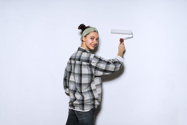 Garota sorridente e feliz fazendo reparos em seu apartamento, pintando paredes de branco