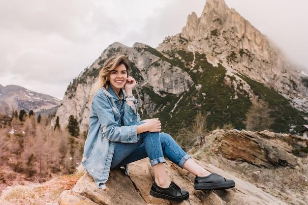 Garota sorridente e inspiradora usando sapatos de couro preto relaxando na pedra após longas caminhadas e posando com prazer