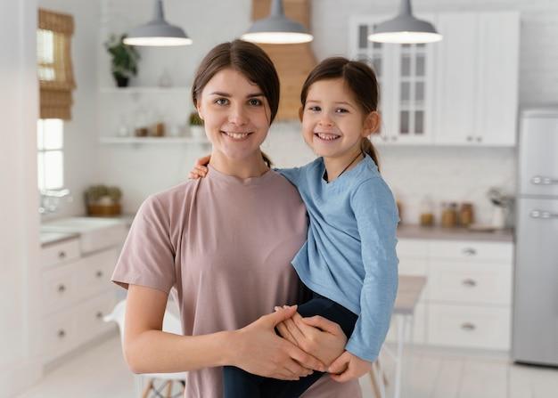 Garota sorridente e mãe posando