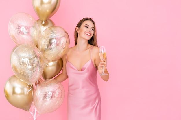 Garota sorridente e sorridente segurando uma taça de champanhe e muitos balões de ar vieram para a celebração da festa
