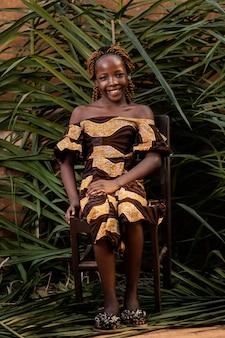 Garota sorridente em foto completa posando na cadeira
