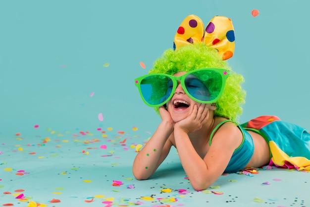 Garota sorridente fantasiada de palhaço com confete e óculos escuros