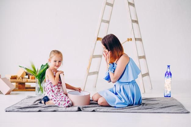 Garota sorridente feliz com a mãe dela descompacta um presente. linda mãe com a filha no quarto decorado branco.