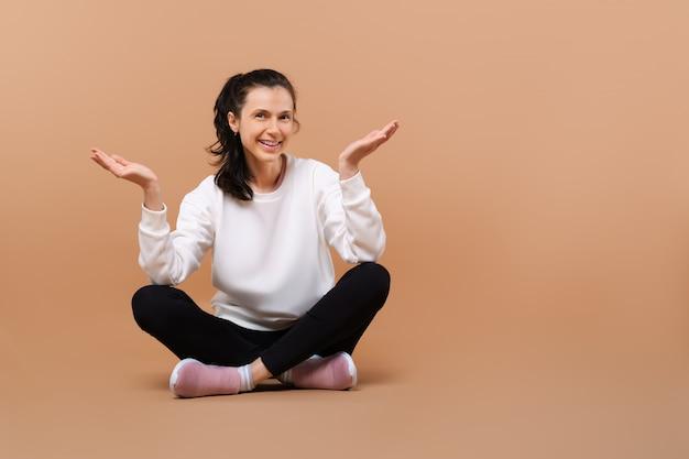 Garota sorridente feliz de camisola branca e legging preta, sentado de pernas cruzadas no chão