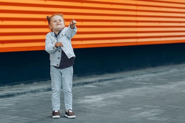 Garota sorridente feliz em jeans, apontando com os dedos