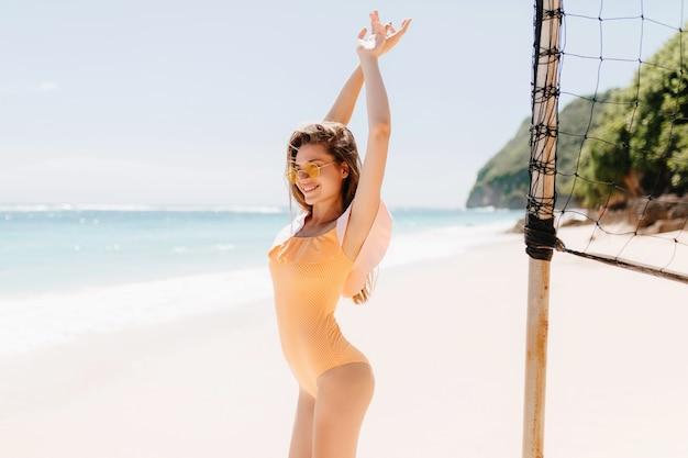 Garota sorridente incrível em trajes de banho, estendendo-se no mar. foto ao ar livre da senhora morena positiva em pé perto de vôlei situado no resort do oceano.