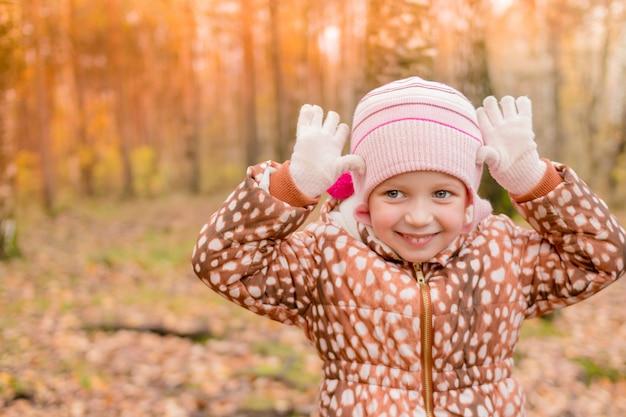 Garota sorridente no casaco no parque, o bebê está mostrando um tigre ou um cervo. criança bonito engraçado