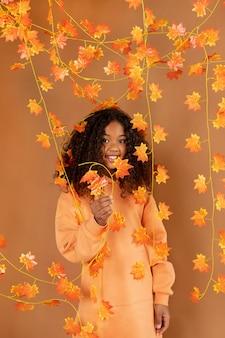 Garota sorridente posando com folhas