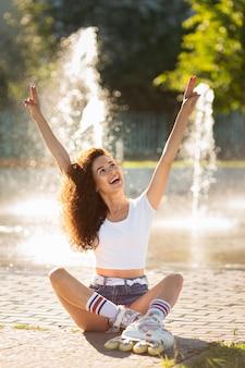 Garota sorridente posando com os braços para cima
