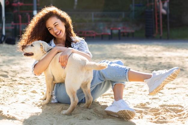 Garota sorridente posando do lado de fora com o cachorro