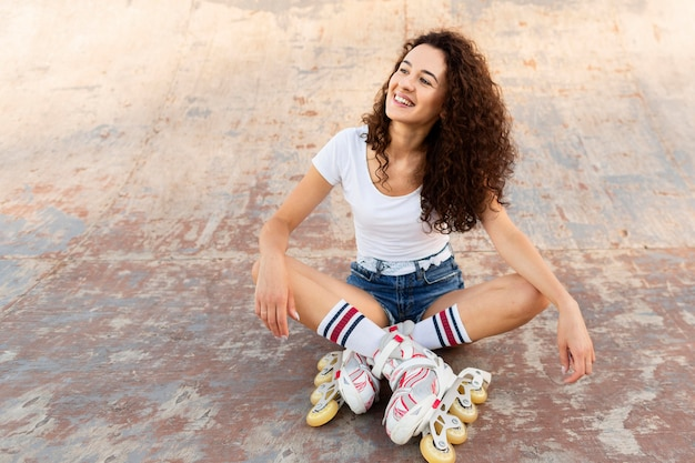 Garota sorridente posando em patins com espaço de cópia