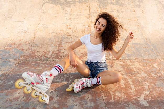 Garota sorridente posando em patins