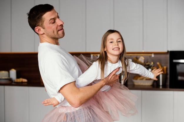 Garota sorridente se divertindo com o pai em saias tutu