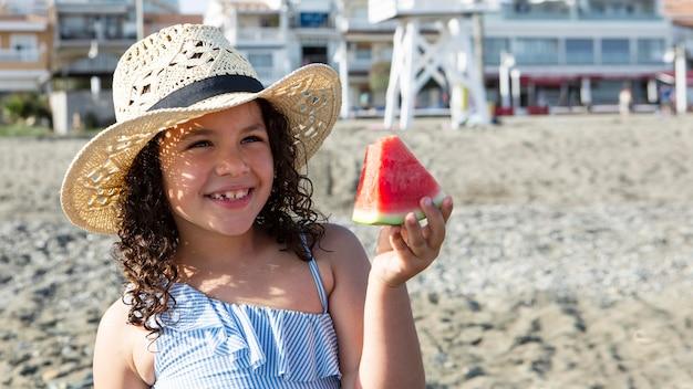Garota sorridente segurando uma fatia de melancia