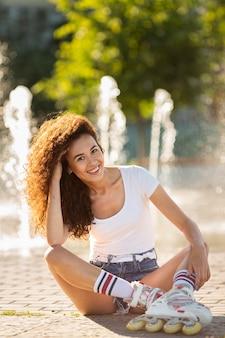 Garota sorridente sentada e posando em patins