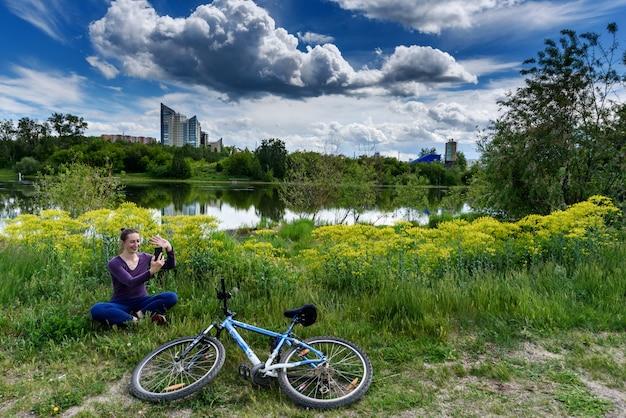 Garota sozinha fala on-line por um link de vídeo perto de sua bicicleta em um parque da cidade. manter distância durante a pandemia de coronavírus.