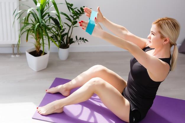 Garota sozinha fazendo exercícios de ioga online no laptop no chão da sala de luz, fique em casa, mundo seguro.