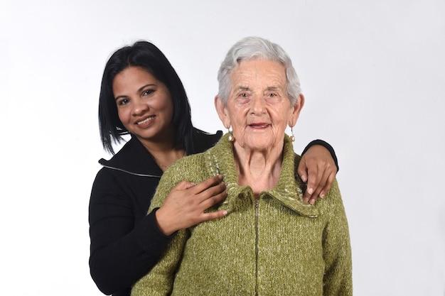 Garota sul-americana cuidando de uma velha em fundo branco