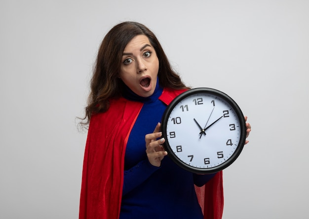 Garota super-heroína caucasiana chocada com capa vermelha segurando um relógio isolado na parede branca com espaço de cópia