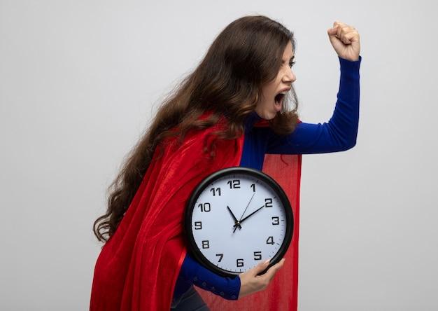 Garota super-heroína caucasiana irritada com capa vermelha fica de lado com o punho levantado e segura o relógio isolado na parede branca com espaço de cópia