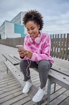 Garota surfa nas redes sociais através de um celular moderno escolhe uma música para ouvir na lista de reprodução usa fones de ouvido usa roupas de estilo de rua poses do lado de fora em um banco de madeira