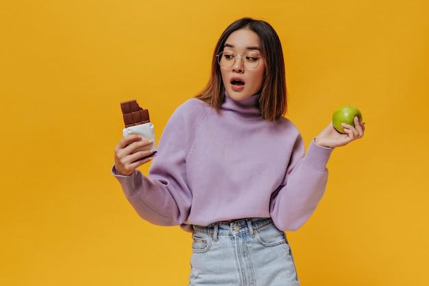 Garota surpresa com cabelos de camisa e óculos olhando para uma barra de chocolate ao leite